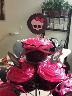 Monster High Cupcakes. Made the picks with printed Logo glued onto black scrap paper then glued onto toothpicks. I dyed the strawberry frosting hot pink.