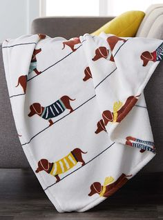 Exclusively from Simons Maison   These whimsical throws are wildly popular! Here, cute sausage dogs delight us with their sweaters and scarves in pop accents on a pure white background.   - Irresistible and ultra comfortable, soft polyester fleece  - 130 x 180 cm