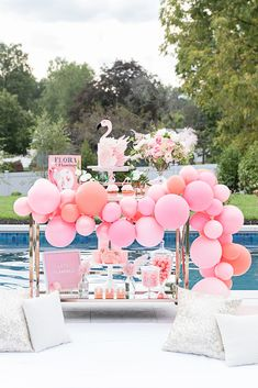 Pretty pink flamingo pool party styled by One Stylish Party featuring a flora the flamingo book, pink balloon garland, insane flamingo cake, pink tropical florals and lots of flamingo partyware by Meri Meri.