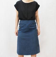 Jupe Céline forme trapèze et taille haute. Deux poches plaquées.Toile de coton épaisse couleur jean. Boutons en métal doré griffés Céline. Taille: 38