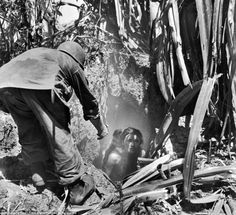 A US soldier offers his hand to a woman leaving a cave where she had hidden with her child, Saipan, 1944. [[MORE]]Project_Ni:She isn't only scared by the war, but also by the Japanese propaganda. The Japanese told everyone that Americans would rape and murder them if captured. According to the PBS Nova documentary, the Japanese government told the citizens that in order to become a United States Marine, you had to murder your parents. American loudspeaker units and American marines