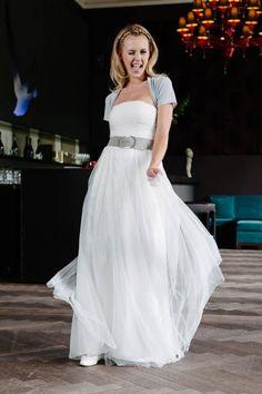 Schlicht und gleichzeitig frech - mit Dottie wird deine Hochzeit zum Vergnügen. Ein Corsagen-Brautkleid mit extravaganter Raffung und Tupfen-Tüll, der begeistert. Genau wie Dotties kleine Verwandlung.