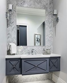 Floating vanity with x detail on cabinets. Gray and white bathroom.