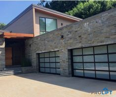 With Full Vision Glass Panels And Black Aluminum Frames These Clopay Avante Garage Doors Perfectly Complement The Exterior Glass Garage Door Black Garage Doors Cottage Front Doors