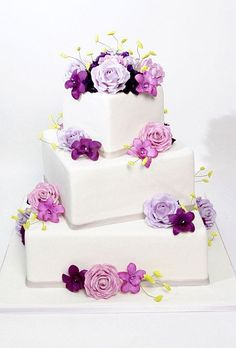 White fondant wedding cake with square tiers decorated with pink and purple roses and orchids. Cake by Carlo's Bakery. | FollowPics