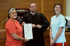 Judge Marc DeRouen introduces Tia Marshall, right, and Holly Pryor after their wedding ceremony at the Jefferson County Sub-Courthouse on Monday. The couple chose to expedite their wedding in angst that the state would repeal the Supreme Court's recent ruling on the matter. The couple are the first to be licensed and wed by the state in Jefferson County.  Photo taken Monday, June 29, 2015  Guiseppe Barranco/The Enterprise Photo: Guiseppe Barranco, Photo Editor