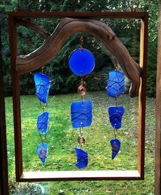 Sun catcher. Made with a wooden frame, small branch, and copper wire.