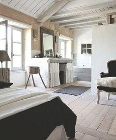 Les poutres apparentes donnent du charme à cette chambre parentale au parquet blanchi et décorée par des couleurs naturelles pour une ambiance douce et apaisante