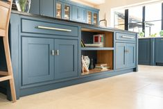 A very large island features lots of storage and nice neat shelves for our client's cookbooks. The gold handles chosen contrast against the beautiful blue of the cabinets perfectly. Shaker Style Kitchens, Shaker Kitchen, Handmade Dressers, Oval Room Blue, Kitchen Triangle, Borrowed Light, Stiffkey Blue, Cornforth White, Shaker Furniture
