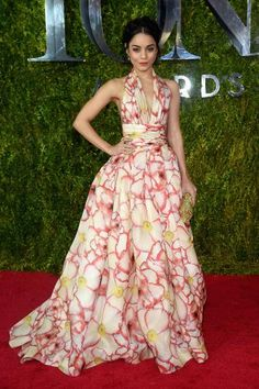Vanessa Hudgens-Tony Awards 2015 The  Gigi actress, who is peforming at the Tony Awards with her cast, looked all grown up on the red carpet in a flowing halter gown with floral print by Naeem Khan. We love her upswept hair and gold Rodo clutch. What a star!