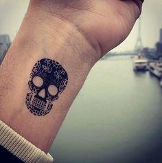 graceful black skull tattoos on the wrist