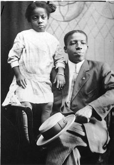 African American man seated in suit with straw hat on his knee. Likely it is his daughter standing beside him. c1920s