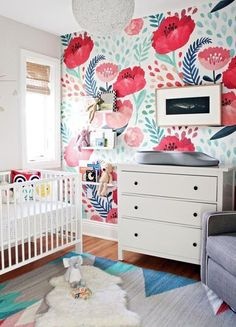 """Boldly patterned walls are popular in nurseries, says Pam Ginocchio, (...)""""They're dramatic, fun, and you can build the rest of your room around them,"""" says Ginocchio. When interior designer Krista Salter was pregnant, she chose not to find out her baby's sex and designed the room to work for either a girl or a boy (hello, neutral base!). Then after her daughter Isla was born, Salter added this bold floral wall to totally transform the room.(...) #poppy #wallmural #wallpaper #nurserydecor"""