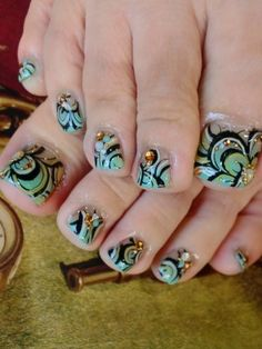 Pretty pedicure: Abstract flower design, Black outline with light green/turquoise/yellow colors. And gold studs to finish out the design. I love this