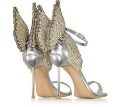 Silver Evangeline Sandals crafted in sparkling silver lame leather with crystal embellishments, have an immaculate silhouette with a fantasy fabulous sensual vibe sure to make a statement. Featuring ankle strap with buckle closure, open toe, lame leather toe strap, laser cut crystal embellished angel wing detail on back heel, silver tone pole stiletto heel and leather sole. Runs a half size small. Signature dust bag included.