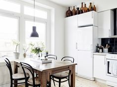 White kitchen with industrial pendant and wood table