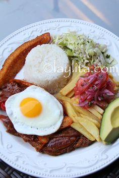 Ecuadorian churrasco steak plate with fried egg, plantains, homemade fries, and salad