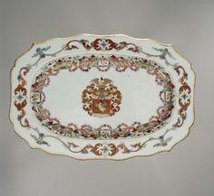 Anonymous | Schotel met het wapen van de familie Falck, Anonymous, c. 1745 - c. 1755 | Langwerpige schotel met een geschulpte rand met in het plat het wapen van de familie Falck; gedecoreerd in ijzerrood, turkooisgroen, blauw, roze en goud. Het wapen heeft een rode achtergrond met daarop een valk afgebeeld. Het helmteken is tevens een valk en het dekkleed bestaat uit bladranken in rood en goud. Op de wand een versiering in Du Paquier-stijl met cartouches, bloemen, guirlandes en valken. Op de…