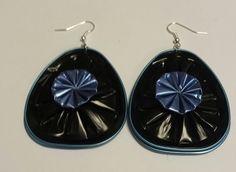 Les boucles d'oreille sont composées de deux capsules de thé en aluminium collées dos à dos. La capsule est noire bordée de bleu avec au centre un sommet de capsule de café - 14706063