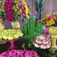 festa mexicana com mesa de doces decorada com flores e letreiro luminoso de cacto. Mais