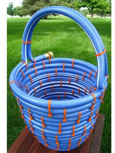 Woven basket from old hoses...fill with garden tools to make a great gift for the gardener in your family