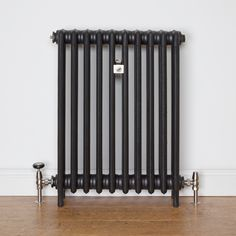 Traditional 4 Column cast iron radiator finished in Matt black and brushed satin radiator valves.