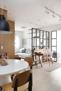 34 Ideias de decoração para Ambientes Integrados sala home office e quarto. Mesa de jantar integrada ao home office e sala de estar e tv. Ambiente dividido com painéis metálicos com vidro. Beje, Branco, Tons de madeira e preto são as cores do ambiente.