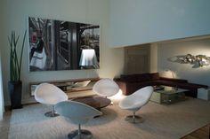 Vista do outro lado da área do home theater, mobiliado com sofá Design, da Dpot, e mesa de centro de vidro, da Silvestre Vidros