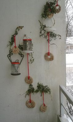 Balcony wall in Helsinki, Finland, with homemade dark rye bread ornaments and frozen snapdragons. Tea candles in the jars make a pretty display at night.