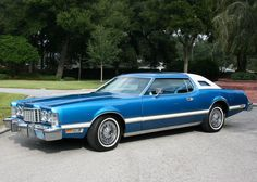 1976 Ford Thunderbird, blue with white vinyl top.