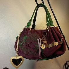 """Juicy Couture Live for Couture Velour satchel Excellent used condition Juicy Couture satchel bag in a vibrant purple with green trim.  Has gold toned Live for Couture bling hanging on the front along with a large purple stone.  Has mirror and two interior pockets but is missing keychain.  Velour is very soft and very clean.  No wear marks, holes, tears or stains.  14"""" w x 8"""" h with a 6"""" drop.  All leather trim in excellent condition.  Has an ink stain on one side of magnet. Juicy Couture…"""