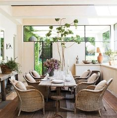 A covered enclosed sun porch in t.v. star Ellen Degeneres' home boasts a rustic dining table surrounded by wicker arm chairs.