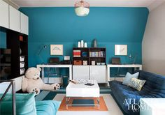 Brian Watford - Blue kids' playroom and homework room features  accent wall painted blue lined with matching white lacquer desks, West Elm Parsons Desk with Drawers, paired with Ikea Tobias Chairs flanking a white lacquered cabinet topped with shelves.