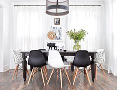 Contemporary dining room features a metal mesh drum chandelier illuminating a dark stained rectangular dining table lined with a mix of black and white dining chairs, Eames Molded Plastic Chairs. Woven Dining Chairs, White Dining Chairs, Dining Room Chairs, Dining Room Furniture, Dining Rooms, Dining Table, Accent Chairs, Office Chairs, Dinner Chairs