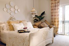 Soft and graceful, the room reflects timeless style with its shades of caramel, coffee, café au lait, and gold. Luxury prevails with the antique bed and hand-printed cotton duvet. Also featured is an oversize chair in a rich caramel-colored fabric with gray trim. Shells, plates, and ornate frames are used as decorative touches.