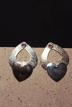 Pezzi unici e artigianali.Orecchini motivo a cuore,in argento lavorato a pelle di serpente,elementi di bronzo e gancio in oro con applicazioni di brillantini.
