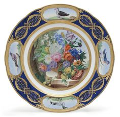 A SEVRES PORCELAIN (LATER-DECORATED) BLUE-GROUND ORNITHOLOGICAL PLATE (ASSIETTE UNIE) THE PORCELAIN 18TH CENTURY, SPURIOUS BLUE INTERLACED L'S AND PAINTER'S MARKS, THE DECORATION LIKELY MID-19TH CENTURY Richly painted with a floral still-life reserved within a gilt band, the border with four birds, named on the underside, each reserved within a gilt cartouche superimposed on entwined laurel garlands enclosing diaper pattern and seeded lozenges at the joins
