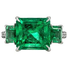 For Sale on 1stDibs - A color-rich three-stone ring showcasing a 4.82 carat emerald cut green emerald, flanked by smaller green emeralds weighing 1.22 carats total. Set in a