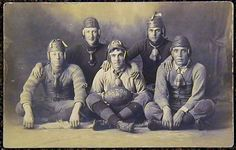 an exceptional Football Photo Postcard that is dated 1909. Featured on this postcard is a group shot of five football players with the one at center holding a plump melon football that is dated 1909. Each player is wearing a vintage leather football helmet... either a flat-top, rain-cap or strap helmet. Also, each player is wearing around his neck a noseguard, four of the five are of the bat-wing variety.