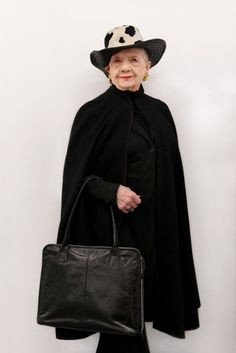 A black cape is worn with black pants, a leather bag, gold earrings, and a spotted hat