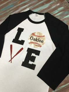 Cool shirt for baseball fans!!!!! Just list your childs name and we can put it right on to the vintage looking baseball. Try one of our comfy Raglan colored sleeve Tees with our Super Sparkly Glitter Vinyl lettering. Our glitter vinyl holds up wash after wash. Sleeve colors available: Red, black, navy, royal, Kelly green, yellow, purple, orange, and, maroon, red/gray, navy/gray, royal/gray, maroon/gray, Hunter green/gray  Sizes S-3X are available. 3/4 length and ...