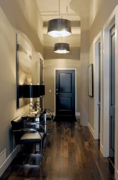 chic, modern foyer entrance design with gray walls paint color, black leather brno flat bar chairs, black drum pendant foyer lights, glossy black door, console table, crystal lamps with black shades and abstract art.