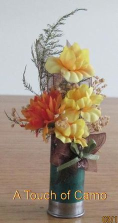 boutonniere  small silk flowers and greens inside a shotgun shell. Pin  glued on backside. 553b6db4b557