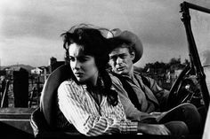 """1955, Marfa, TX– Elizabeth Taylor and James Dean in a scene from George Stevens' film, """"Giant.""""George Stevens had such luck with Elizabeth Taylor in 1951′s """"A Place in The Sun"""" that he cast her once more in the epic, """"Giant"""" years later. It was Taylor's first epic film and she was playing opposite Rock Hudson and James Dean. She formed separate ,intense relationships with both of the famous actors– who were quite different in regard to talent and personality."""