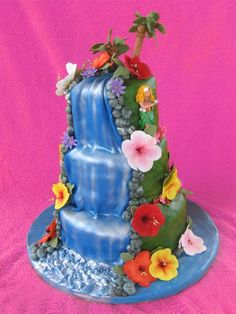 Waterfall Cake Three tier cake covered with fondant and decorated with gumpaster flowers, palm trees, & dancers.