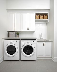 All white laundry room, subway tile backsplash, white cabinets, large sink, wicker baskets | Albert David Design Inc.