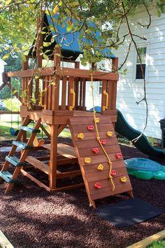 Small backyard playground with rubber mulch. #RoosterRubber #playsafe #playground #slide #mats #backyard #mulch #fort