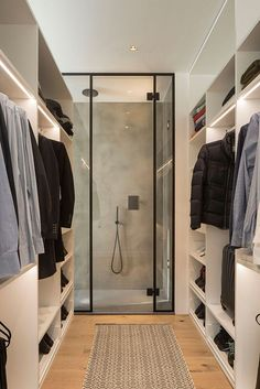 This modern walk-in closet has a black framed, glass shower at one end, while some of the shelves in the closet have strips of lighting to add additional light to the space.