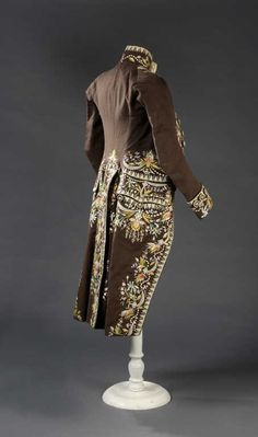 Rear view, coat and breeches (habit à la francaise), France, late 18th century. Dark bronw woll plaisn weave, lavishely embroidered with floral motifs and garlands in polychrome silk, fabric covered and embroidered buttons.