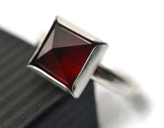 This hessonite garnet pyramid ring is made to order and ships in 7 business days. Gemstone: 10mm x 10mm pyramid cut dark red hessonite garnet. Traditionally believed to be a stone of protection, success, clarity and courage. Ring: Sterling Silver Square Bezel Setting, Sterling Silver 3mm Wide Hammered Band. Care Advice & Complimentary Polishing Cloth Included Packaged in protective box. Signature may be required upon delivery. If you are sensitive to metal we will happily lacquer the ins...
